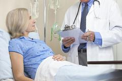 Senior female patient in hospital bed & male doctor Stock Photos