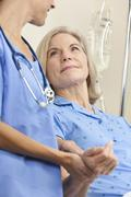 Senior female patient in hospital bed & woman doctor Stock Photos
