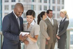 Interracial men & women business team with tablet computer Stock Photos
