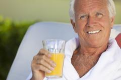 Healthy happy senior man drinking orange juice Stock Photos