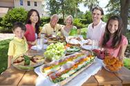 Stock Photo of parents grandparents children family healthy eating outside