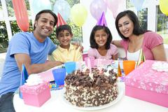 Asian indian family celebrating birthday party with chocolate cake Stock Photos