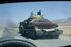 Tank and small car on transporter near Kabul, Afghanistan. Stock Photos