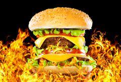 Tasty hamburger on fire on a dark Stock Photos
