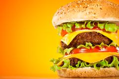 Stock Photo of tasty and appetizing hamburger on a yellow