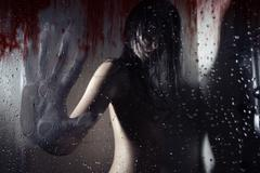 werewolf in the dark bathroom touching wet bloody glass by his huge hand with - stock photo