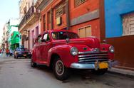 Stock Photo of vintage red car on the street of old city, havana, cuba