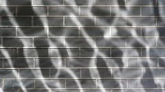 Caustic water reflections of sunlight on a brick wall. - stock footage