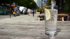 Fizzy drink with ice and lemon with a busy city background. Stock Footage