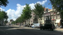 Netherlands Amsterdam blue streetcar passes gabled building - stock footage
