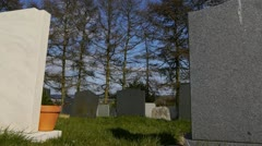 Camera tracks past some gravestones ending on a big white marble gravestone. Stock Footage