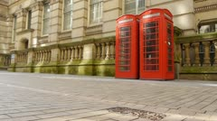Two red english telephone boxes with a Classical architecture background. Stock Footage