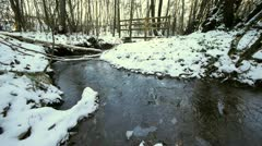 A small footbridge over a stream which is partly frozen. Stock Footage