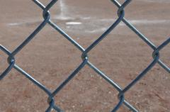 Home plate baseball behind chain link fence Stock Photos