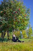 Woman under mountain ash tree Stock Photos