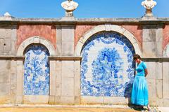 Girl in blue dress near wall with blue azulejo Stock Photos