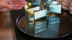 Hand takes candle in candleholder and ignites it by lighter - stock footage