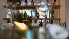 Bottles on shelf in restaurant with glasses and candle at table Stock Footage