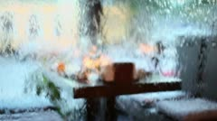 Table behind waterwall in cafe and cars on street beyond window Stock Footage
