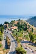 View on town taormina and resort giardini naxos, sicily with conifers Stock Photos