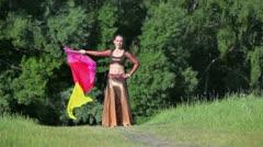Woman in smart dress dances with rhipidium near forest Stock Footage