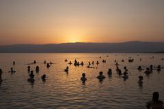 People float in the dead sea during sunrise Stock Photos
