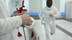 Fencer with rapier puts on glove during training in gym Stock Footage