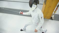 Fencer attacks with rapier during training in gym, closeup view Stock Footage