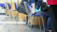 Woman covers her waist when she sit at chair near office desks Stock Footage