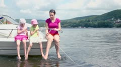 Woman with children sit at boats bow and splashes feet Stock Footage