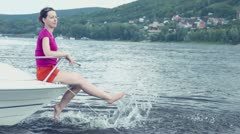 Woman sits at boats bow and splashes feet near coastal town Stock Footage