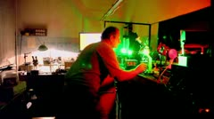 Man watches on display and adjusts laser  in laboratory Stock Footage