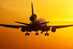 Cargo plane landing in sunrise - stock photo