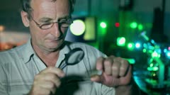 Man hold loupe and watch on glass with probe substance in lab Stock Footage