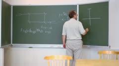 Professor writes scheme on board with formulas Stock Footage