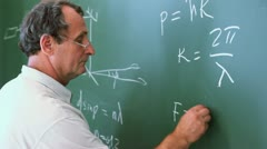 Professor writes formulas for force of Newtons second law - stock footage