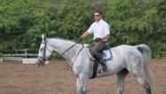 Horseman rides on horseback by equestrian field Stock Footage