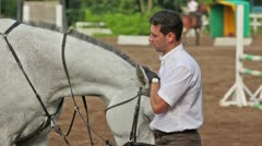 Man pats horse head and then lead it away on equestrian field Stock Footage