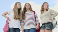 Three girls with handbags stand together and watch sideward - stock footage