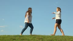 Two young girls embrace and raise each other on grass hill Stock Footage