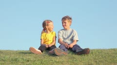 Two kids boy with little girl sit and talk on grass hill Stock Footage