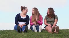 Three girls sit and talk on grass hill at sunny summer day Stock Footage