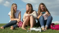 Girls with bags listen music from cell phones and sing on hill Stock Footage