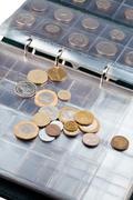 numismatics album with different coins - stock photo