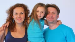 Father with mother hold daughter who smiles and puts out tongue Stock Footage