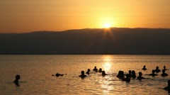 People float in the dead sea during sunrise Stock Footage