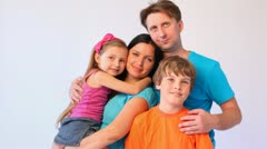 Father, mother, daughter and son stands together embracing Stock Footage