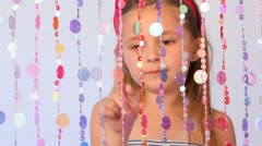 Girl behind curtain from threads with round plates counts them Stock Footage