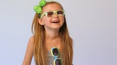 Little girl wearing spectacles and on dress holds in each hand Stock Footage