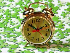 Alarm clock on the green puzzle Stock Photos